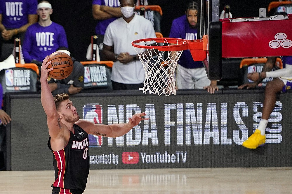FILE - In this Oct. 4, 2020, file photo, Miami Heat's Meyers Leonard (0) shoots against the Los Angeles Lakers during the second half in Game 3 of basketball's NBA Finals in Lake Buena Vista, Fla. Leonard and Goran Dragic have both decided to return to the Eastern Conference champions, each telling The Associated Press on Friday evening, Nov. 20, 2020, that they have agreed to accept Miami's offer of two-year deals -- the second year is a team option on both contracts -- to remain with the Heat. (AP Photo/Mark J. Terrill)