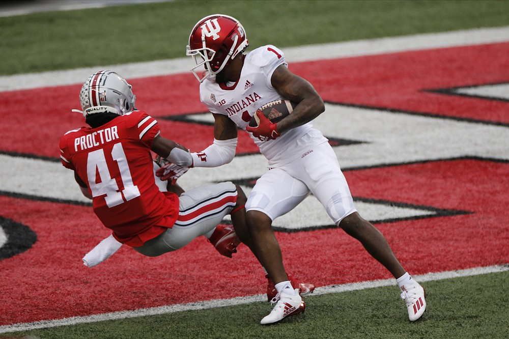 Indiana receiver Whop Philyor, right, forces his way into the end zone past Ohio State defensive back Josh Proctor during the first half of an NCAA college football game Saturday, Nov. 21, 2020, in Columbus, Ohio. (AP Photo/Jay LaPrete)