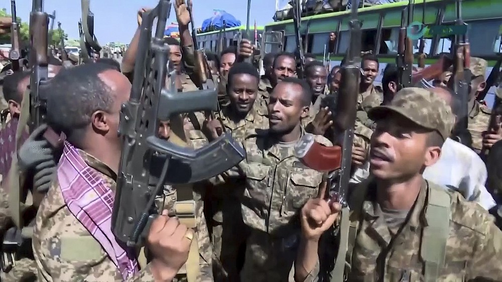 """This image made from undated video released by the state-owned Ethiopian News Agency on Monday, Nov. 16, 2020 shows Ethiopian military cheering and dancing in front of cameras on a road in an area near the border of the Tigray and Amhara regions of Ethiopia. Ethiopia's prime minister Abiy Ahmed said in a social media post on Tuesday, Nov. 17, 2020 that """"the final and crucial"""" military operation will launch in the coming days against the government of the country's rebellious northern Tigray region. (Ethiopian News Agency via AP)"""