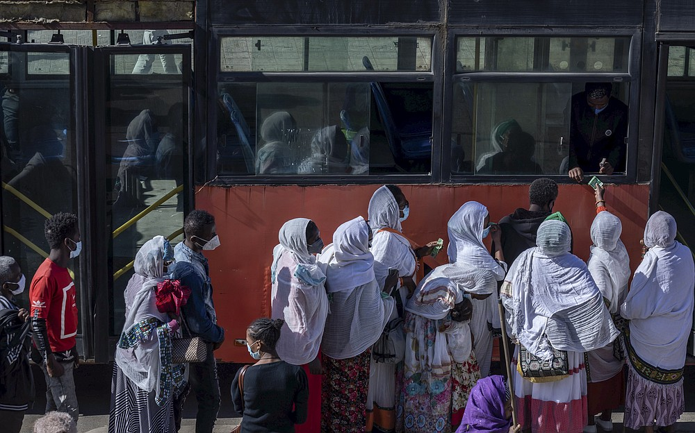 """Passengers queue to get on a bus in the capital Addis Ababa, Ethiopia Friday, Nov. 6, 2020. Ethiopia's prime minister says airstrikes have been carried out against the forces of the country's Tigray region, asserting that the strikes in multiple locations """"completely destroyed rockets and other heavy weapons."""" (AP Photo/Mulugeta Ayene)"""