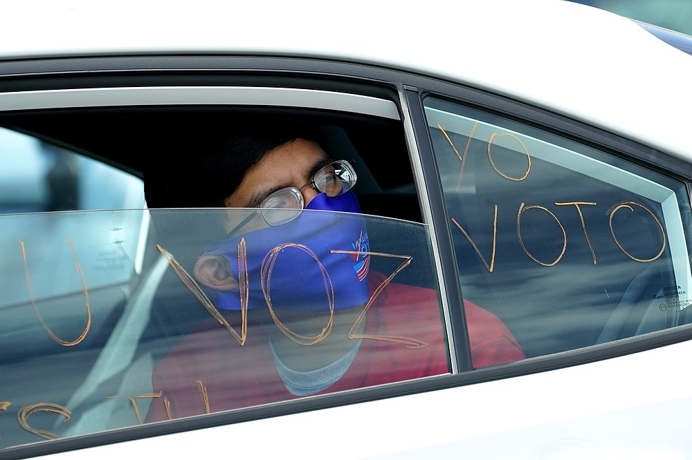 """FILE - In this Aug. 13, 2020, file photo a man looks out of a car window as he takes part in a car rally at the Capitol in Phoenix. """"We are at a point where there was no pathway to victory"""" for Democrats without support from voters of color, said Alejandra Gomez, co-executive director of the political group Living United for Change in Arizona. """"Our terrain has forever changed in this country in terms of the electoral map. (AP Photo/Matt York, File)"""