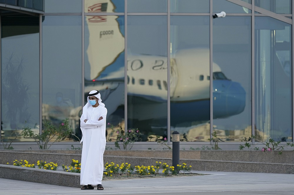 A man stands on a tarmac as Secretary of State Mike Pompeo's plane is reflected in windows at Al Bateen Executive Airport in Abu Dhabi, United Arab Emirates, Friday, Nov. 20, 2020. Pompeo is visiting the United Arab Emirates as part of a seven-nation trip to Europe and the Middle East. (AP Photo/Patrick Semansky, Pool)
