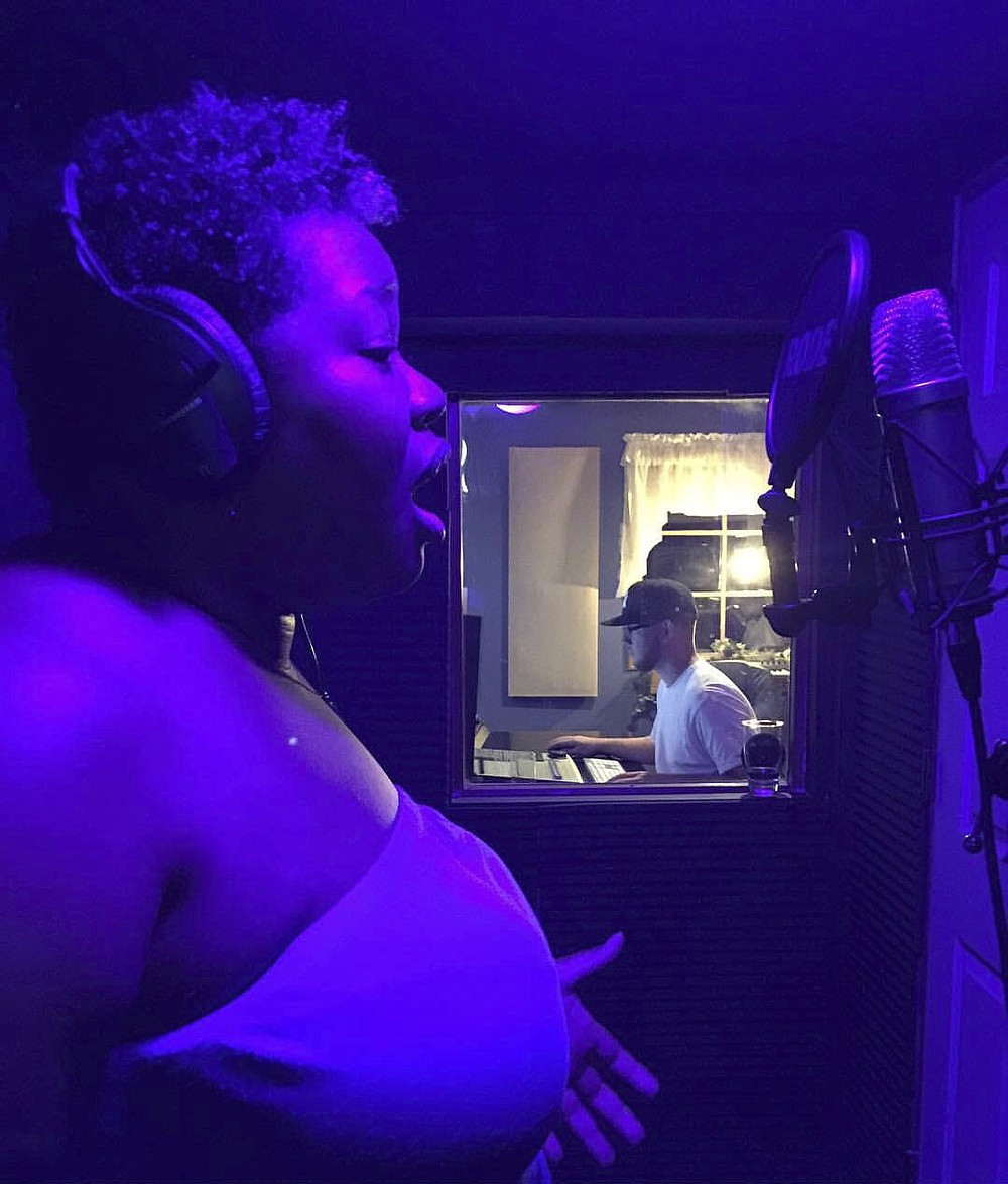 This undated image shows Rashida Bryant singing at a home recording studio in Long Island, N.Y. Bryant, 44, is an Atlanta-based voice instructor through Wyzant,  an online marketplace for private tutors, who saw her client roster double from April to June, when she had 30 students. Her students range in age from early teenagers to people in their late 60s.   (Kiki Bryant  via AP)