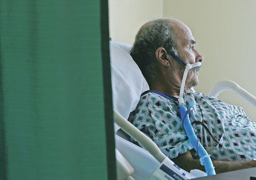 A COVID-19 patient sits in his hospital bed at the El Paso Long Term Acute Care Hospital, Friday, Nov. 6, 2020, in central El Paso, Texas. El Paso is seeing a spike in coronavirus cases. (Mark Lambie/The El Paso Times via AP)
