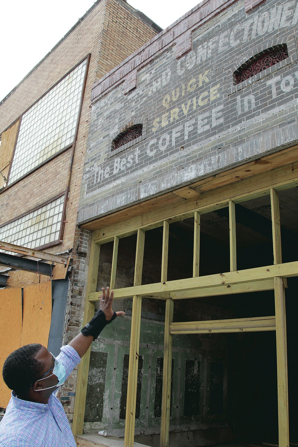 """Maurice Taggart points to the signage that was revealed when the facade was removed from the facing of the building at 324 Main St. """"I told them the leave it up there,"""" Taggart said. """"I like the historical authenticity that it gives the building."""" (Pine Bluff Commercial/Dale Ellis)"""