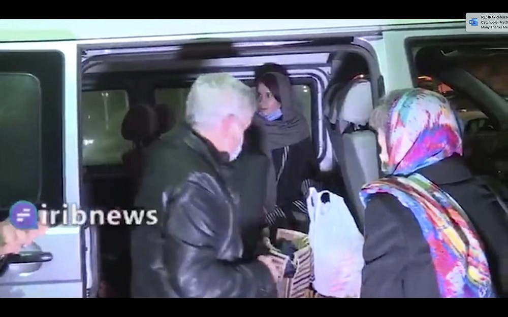 In this frame grab from Iranian state television video aired Wednesday, Nov. 25, 2020, British-Australian academic Kylie Moore-Gilbert, center inside van, is seen in Tehran, Iran. Iran has freed Moore-Gilbert, who has been detained in Iran for more than two years, in exchange for three Iranians held abroad, state TV reported Wednesday. (Iranian State Television via AP)