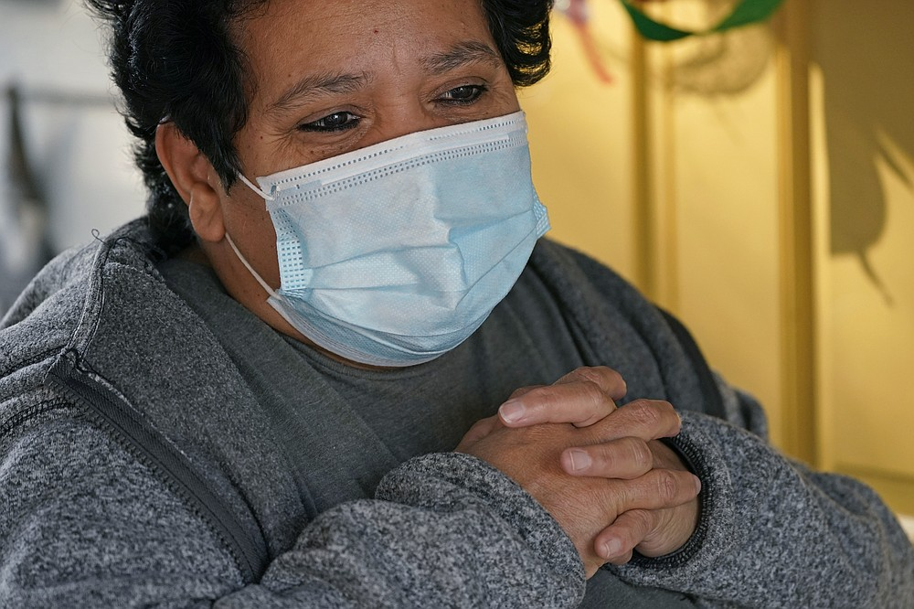 Evelyn Maysonet, 53, looks on as food is provided by Weber-Morgan Health Department Tuesday, Nov. 24, 2020, in Ogden, Utah. Maysonet has been isolating with her husband and son in their Ogden home since all three tested positive for COVID-19 over a week ago. None of them have been able to leave home to buy groceries so Maysonet said they were thrilled to receive the health department's delivery. (AP Photo/Rick Bowmer)