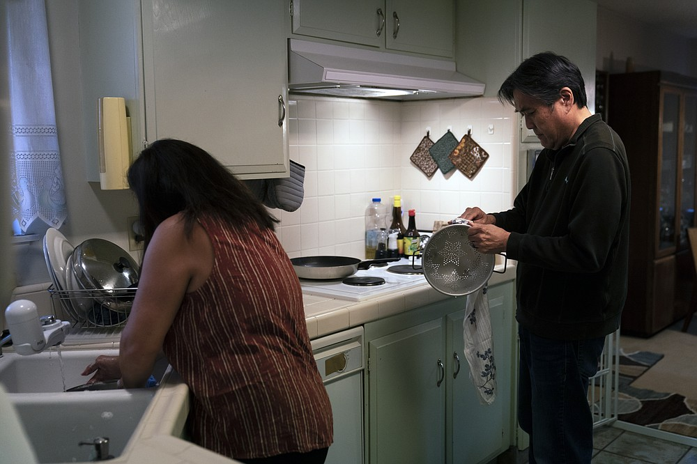 Kerry Osaki, right, helps his wife, Lena Adame, in the kitchen in Fountain Valley, Calif., Wednesday, Nov. 25, 2020. For years, Osaki went with his mother to his aunt's house for Thanksgiving to celebrate with family. His wife spent the holiday cooking a spread of turkey and stuffing with her relatives. This year, both of their traditions have fallen to the pandemic that took the life of Osaki's 93-year-old mother.(AP Photo/Jae C. Hong)