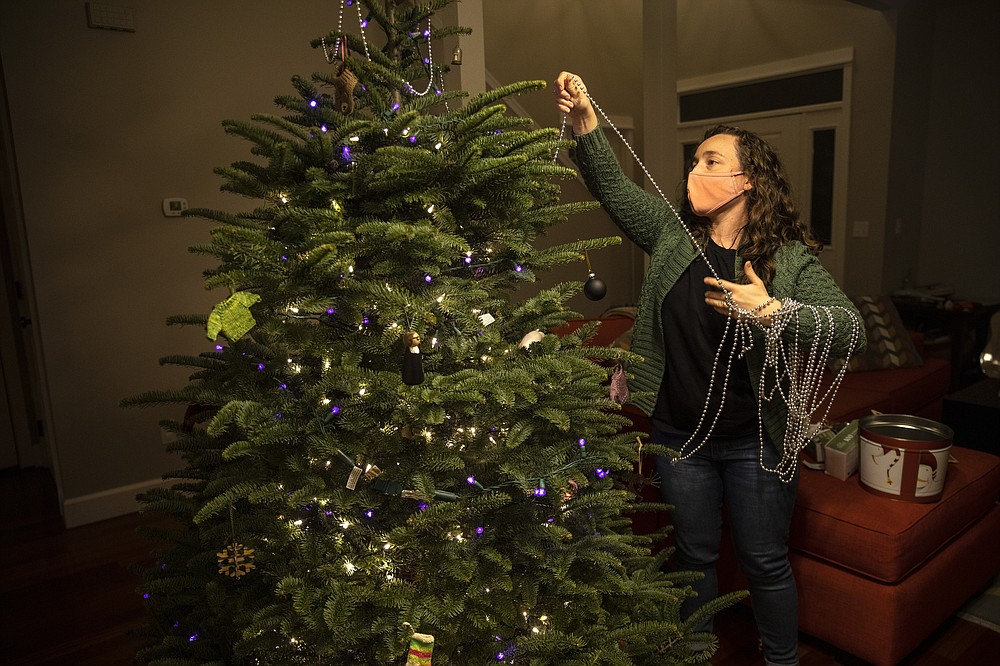 Ani Sirois puts lights and decorations on the family's Christmas tree at her home on Tuesday, Nov.  24, 2020 in Portland, Ore.   Sirois, a respiratory nurse, has spent months caring for coronavirus patients at a Portland hospital. But on a recent sunny day, COVID-19 seemed far away as she, her husband and their 2-year-old daughter roamed a Christmas tree farm in search of the perfect evergreen for a holiday season unlike any other. The family was tree-shopping nearly a week before Thanksgiving and, for the first time, they were picking their own tree instead of buying a pre-cut one. (AP Photo/Paula Bronstein)