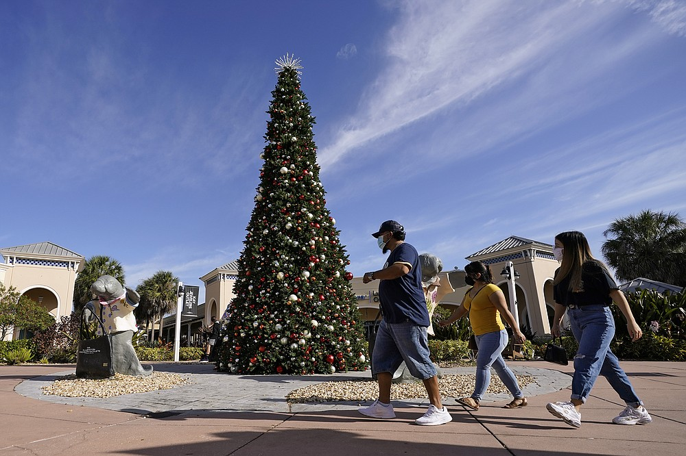 Shoppers wear protective face masks as they walk past a Christmas setting at the Ellenton Premium Outlet stores Friday, Nov. 27, 2020, in Ellenton, Fla. Attendance at the mall was down in an attempt to avoid spreading the corona virus. (AP Photo/Chris O'Meara)