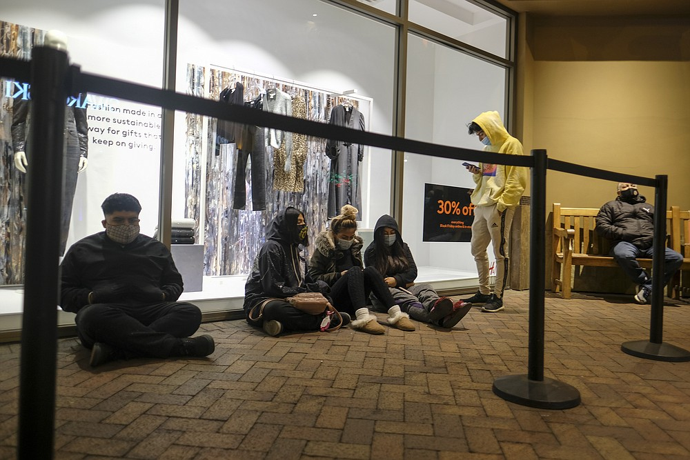 Black Friday shoppers wait in line to enter an shore that opened at 6am at the Citadel Outlets in Commerce, Calif., Friday, Nov. 27, 2020. (AP Photo/Ringo H.W. Chiu)