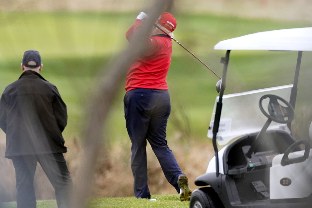 President Donald Trump takes a practice swing as he plays golf at Trump National Golf Club, Friday, Nov. 27, 2020, in Sterling, Va. (AP Photo/Alex Brandon)