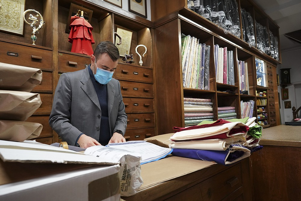 A shop attendant prepares orders in the Gammarelli clerical clothing shop, in Rome, Thursday, Nov. 26, 2020. The consistory to elevate new cardinals scheduled for Saturday, Nov. 28, in the time of coronavirus is like nothing the Holy See has ever seen. A handful of soon-to-be cardinals are in protective coronavirus quarantine, including African-American, Cardinal-designate Wilton Gregory, archbishop of Washington who explained that a U.S.-based ecclesiastical tailor took his measurements while he was still in Washington and sent them to Gammarelli, which then made them to order and sent them to Santa Marta hotel where he is undergoing the quarantine. (AP Photo/Andrew Medichini)
