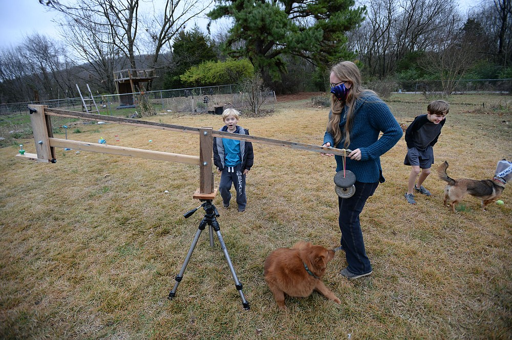 Roslyn Imrie (center) repositions a boom Wednesday that her husband made to steady a pair of binoculars so the whole family can view things in the night sky as her sons Elo Eaton, 7, (left) and Zane Eaton, 11, play outside their home in Fayetteville. Zane and Elo are both on the autism spectrum which complicates learning from home. Visit nwaonline.com/201129Daily/ for today's photo gallery.  (NWA Democrat-Gazette/Andy Shupe)
