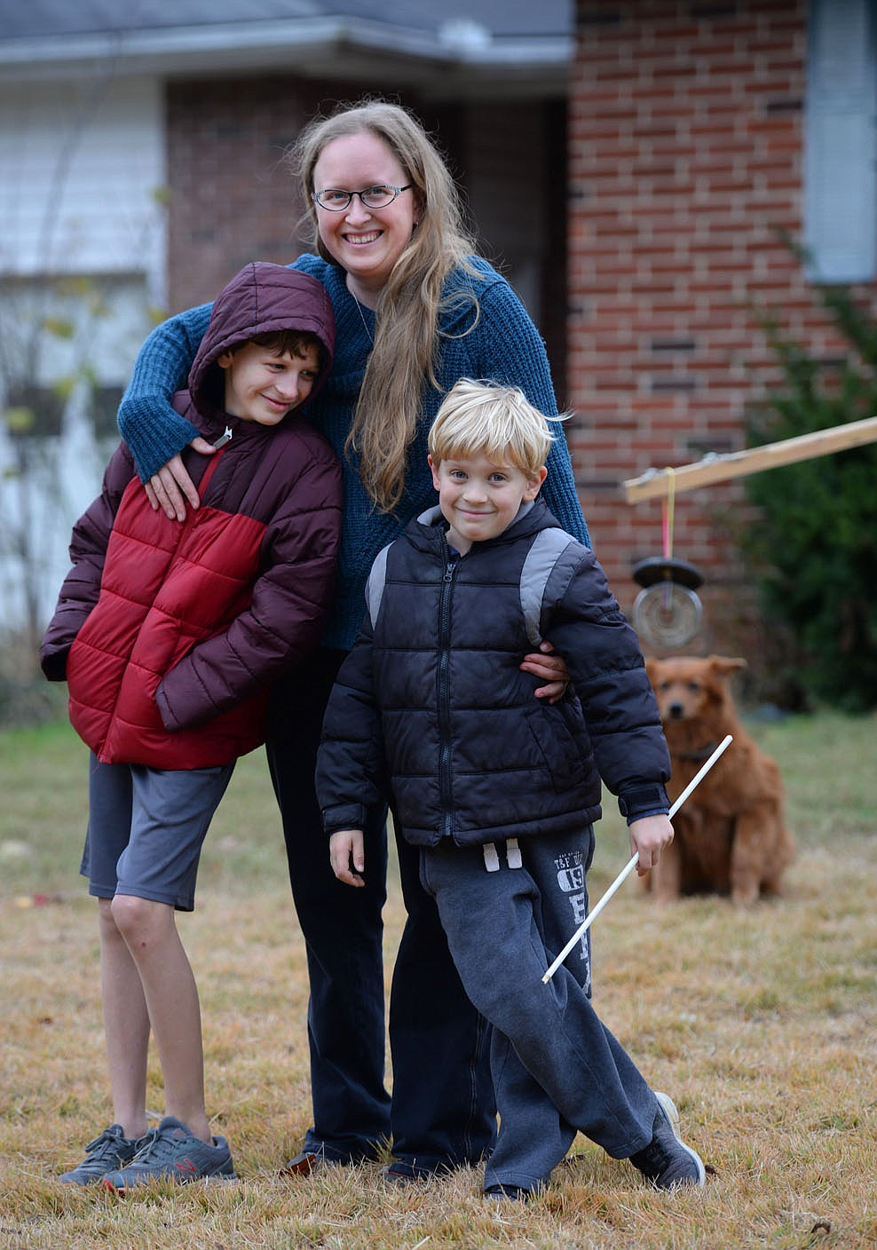 Roslyn Imrie smiles Wednesday as she is photographed with her sons Zane Eaton, 11, (left) and Elo Eaton, 7, outside their home in Fayetteville. The unique sort of instruction normally available ESL and alternative-learning students is difficult to replicate at home. Visit nwaonline.com/201129Daily/ for today's photo gallery.  (NWA Democrat-Gazette/Andy Shupe)