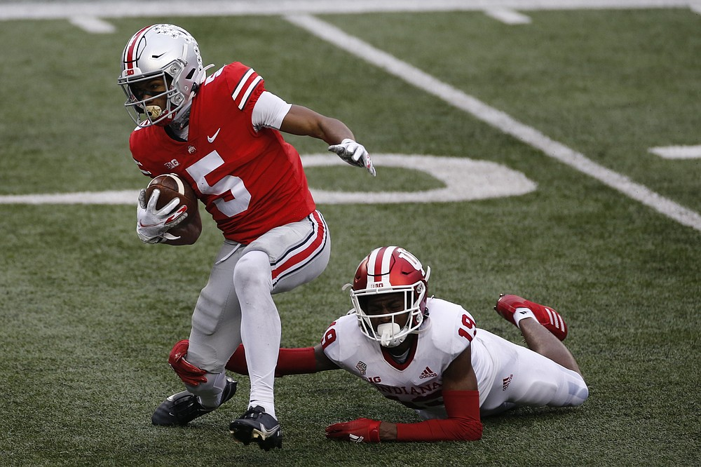 Ohio State receiver Garrett Wilson, left, tries to get away from Indiana defensive back Josh Sanguinetti during the second half of an NCAA college football game Saturday, Nov. 21, 2020, in Columbus, Ohio. Ohio State beat Indiana 42-35. (AP Photo/Jay LaPrete)