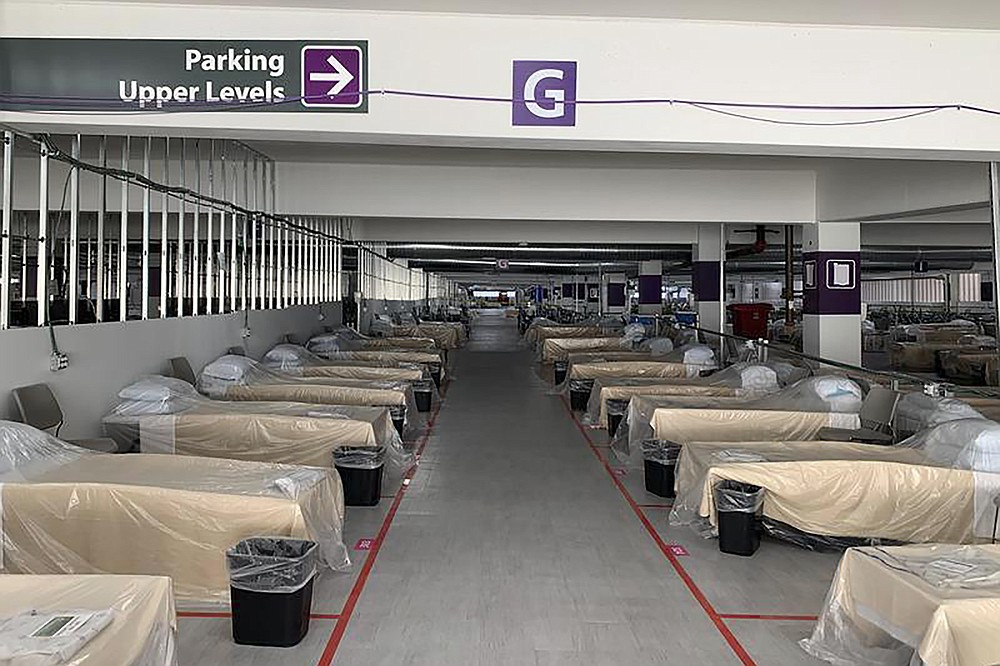 FILE - Hospital beds sit inside Renown Regional Medical Center's parking garage, which has been transformed into an alternative care site for COVID-19 patients in Reno, Nev., on Wednesday, Nov. 11, 2020.  Faulting inaction in Washington, governors and state lawmakers are racing to get needed pandemic relief to small businesses, the unemployed, renters and others affected by the widening coronavirus outbreak. In some cases, they are figuring out how to spend the last of a federal relief package passed in the spring as an end-of-year deadline approaches and the current COVID-19 surge threatens their economies once again.   (Lucia Starbuck/KUNR Public Radio/Report for America via AP)