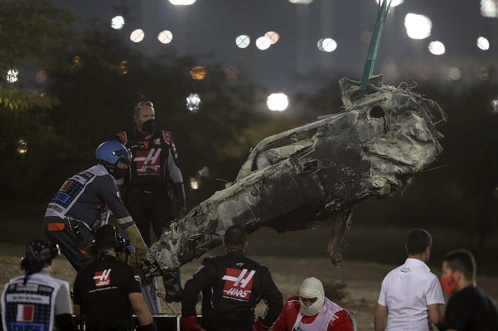 A part of Haas driver Romain Grosjean's car is taken after the crash at the start of the Formula One Bahrain Grand Prix in Sakhir, Bahrain, Sunday, Nov. 29, 2020. (Tolga Bozoglu, Pool via AP)