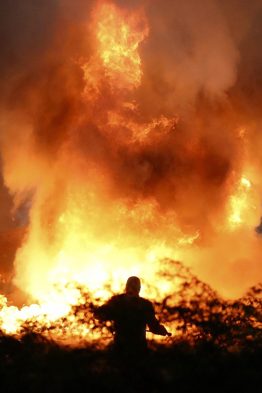 Staff extinguish flames from Haas driver Romain Grosjean of France's car after a crash during the Formula One race in Bahrain International Circuit in Sakhir, Bahrain, Sunday, Nov. 29, 2020. (Bryn Lennon, Pool via AP)