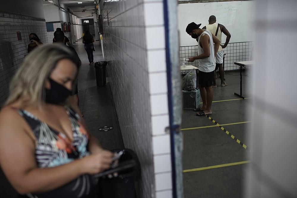 Locals vote at a polling station during run-off municipal elections in Rio de Janeiro, Brazil, Sunday, Nov. 29, 2020. (AP Photo/Silvia Izquierdo)