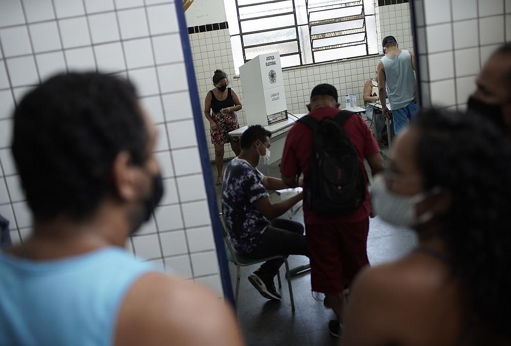 Locals vote at a polling station during the run-off municipal elections in Rio de Janeiro, Brazil, Sunday, Nov. 29, 2020. (AP Photo/Silvia Izquierdo)