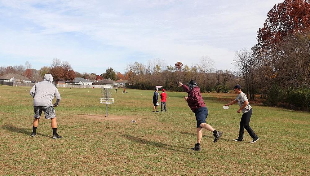 LYNN KUTTER ENTERPRISE-LEADER Players competing in a disc golf tournament at Creekside Park warm up on the course's practice basket.