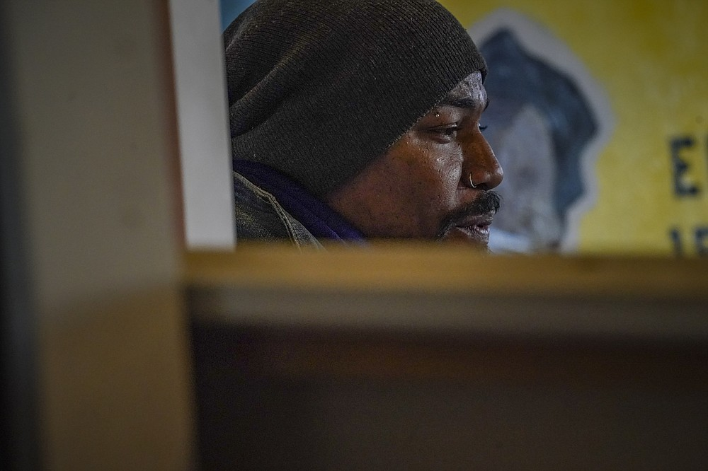 """Painter Guy Stanley Philoche, a 43-year-old Haitian immigrant and star in the New York art world, sit among work during an interview at his East Harlem studio, Thursday Nov. 19, 2020, in New York. After a hugely successful gallery show, Philoche wanted to treat himself to a fancy $15,000 watch, instead he bought the works of fellow artists struggling in the pandemic. """"I'm not a rich man,"""" he said, """"but I owe a big debt to the art world."""" (AP Photo/Bebeto Matthews)"""