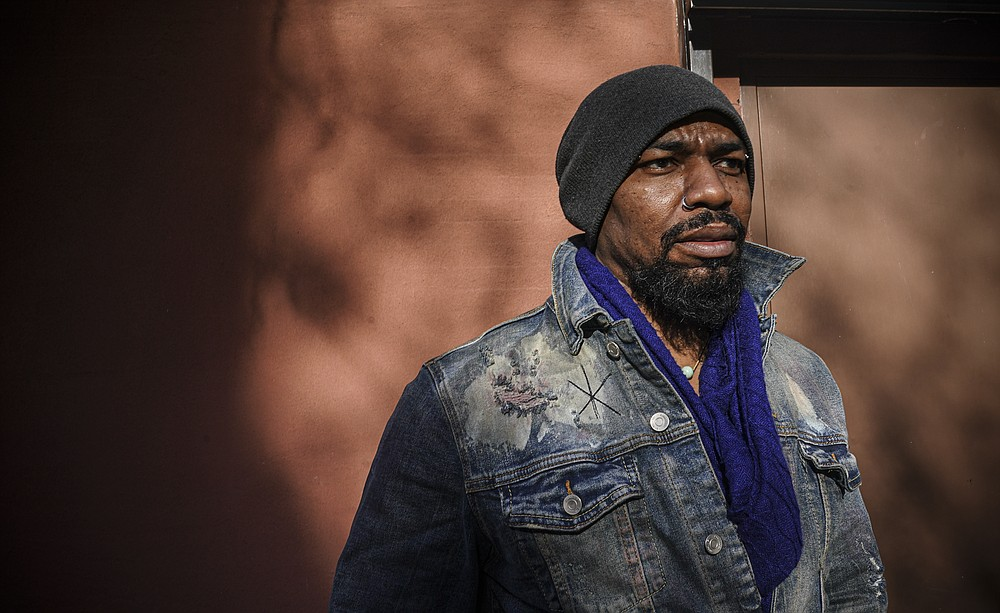 """Painter Guy Stanley Philoche, a 43-year-old Haitian immigrant and star in the New York art world, pose outside his East Harlem studio, Thursday Nov. 19, 2020, in New York. After a hugely successful gallery show, Philoche wanted to treat himself to a fancy $15,000 watch, instead he bought the works of fellow artists struggling in the pandemic. """"I'm not a rich man,"""" he said, """"but I owe a big debt to the art world."""" (AP Photo/Bebeto Matthews)"""