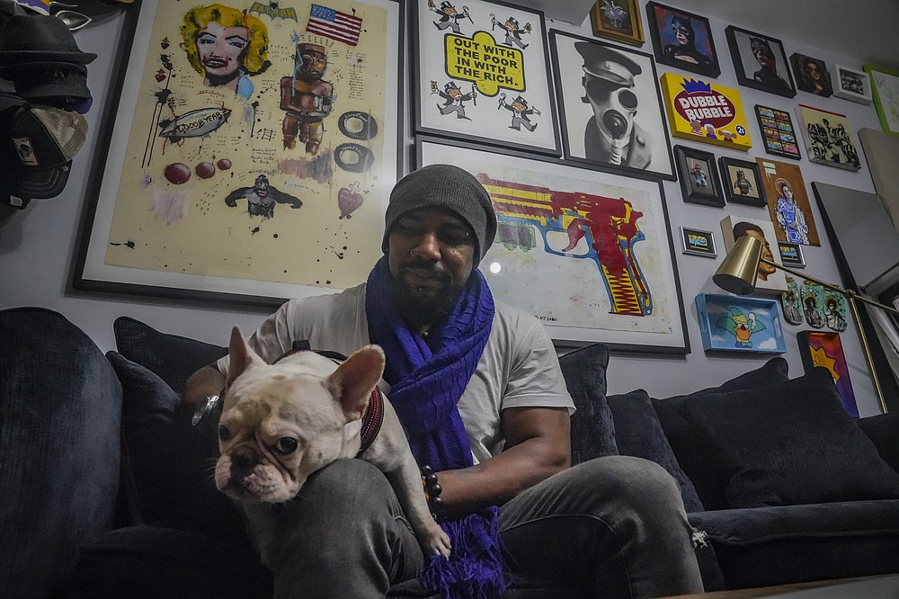 """Painter Guy Stanley Philoche, a 43-year-old Haitian immigrant and star in the New York art world, sits with his dog Picasso at their East Harlem home next to a wall of art collected from other artist, Thursday Nov. 19, 2020, in New York. After a hugely successful gallery show, Philoche wanted to treat himself to a fancy $15,000 watch, instead he bought the works of fellow artists struggling in the pandemic. """"I'm not a rich man,"""" he said, """"but I owe a big debt to the art world."""" (AP Photo/Bebeto Matthews)"""