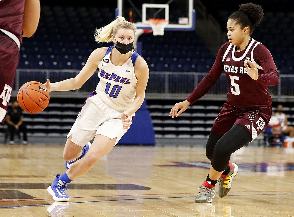 In this photo provided by DePaul Athletics, DePaul's Lexi Held (10) drives as Texas A&M's Jordan Nixon (5) defends during a women's NCAA college basketball game on Saturday, Nov. 28, 2020, in Chicago. It's a common sight to see players and coaches wear masks on the sideline so far this season during college basketball games to help prevent the spread of the coronavirus. The DePaul and Creighton women's basketball teams are among a few squads that have taken it a step further with their players wearing the masks while they are on the court playing. (Steve Woltmann/DePaul Athletics via AP)