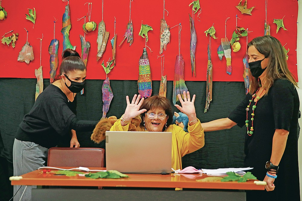 Ioanna Kabouri principal, center, raises her hands as teachers Aphrodite Tzevelekou, left, and Sofia Galiotou perform live an online puppet show for students at a kindergarten in Athens, Thursday, Nov. 19, 2020. Most other European countries have vowed to keep schools open, but the pandemic has hit Greece hard for the first time in recent weeks following a successful lockdown in the spring, overwhelming hospitals in parts of the country. State television is making and broadcasting lessons, while teachers sit in empty classrooms talking to remote students. Despite some problems, they say it keeps children in touch with their schools. (AP Photo/Thanassis Stavrakis)
