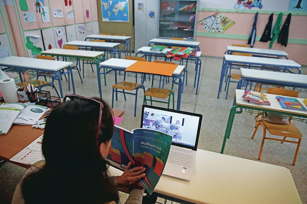 Teacher Aleka Michou gives an online lesson to C class students in an empty classroom of elementary school in Athens, Friday, Nov. 20, 2020. Most other European countries have vowed to keep schools open, but the pandemic has hit Greece hard for the first time in recent weeks following a successful lockdown in the spring, overwhelming hospitals in parts of the country. State television is making and broadcasting lessons, while teachers sit in empty classrooms talking to remote students. Despite some problems, they say it keeps children in touch with their schools. (AP Photo/Thanassis Stavrakis)