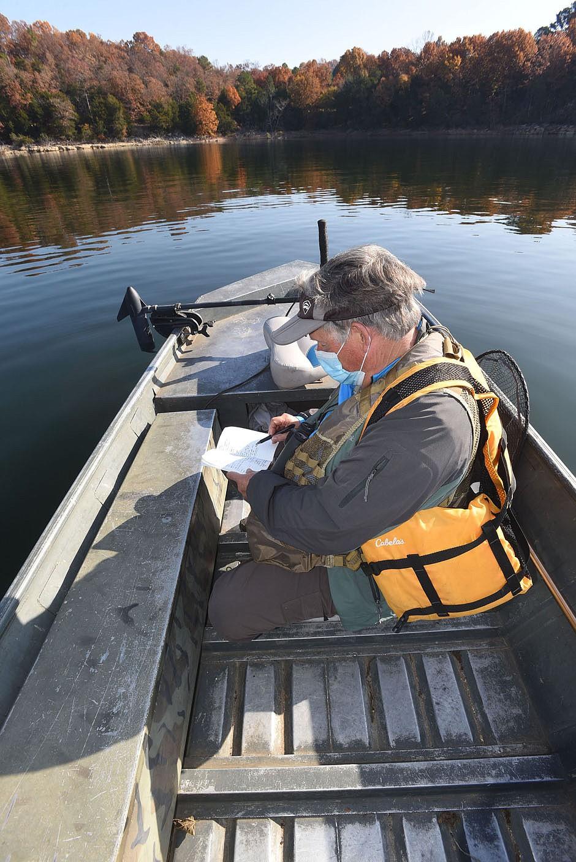 Neal jots down bird species seen Nov. 6 2020 during a morning of birding on Beaver Lake. (NWA Democrat-Gazette/Flip Putthoff)