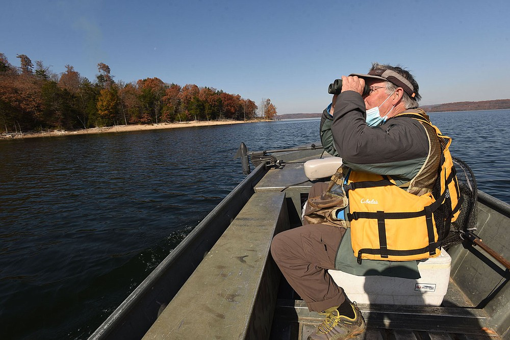 Joe Neal of Fayetteville looks for birds flying high Nov. 6 2020 over Beaver Lake. Neal looked for birds near Rocky Branch park, one of the top birding destinations on the lake. Neal found raptors, waterfowl and songbirds during a morning of birding by boat. Go to nwaonline.com/201208Daily/ to see more photos. (NWA Democrat-Gazette/Flip Putthoff