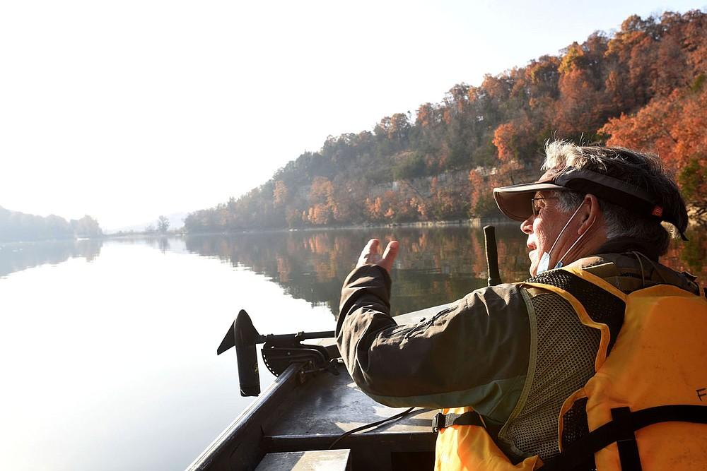 A calm, sun-splashed morning Nov. 6 2020 proved ideal for birding by boat. Joe Neal looks for birds near Rocky Branch park on Beaver Lake. (NWA Democrat-Gazette/Flip Putthoff)