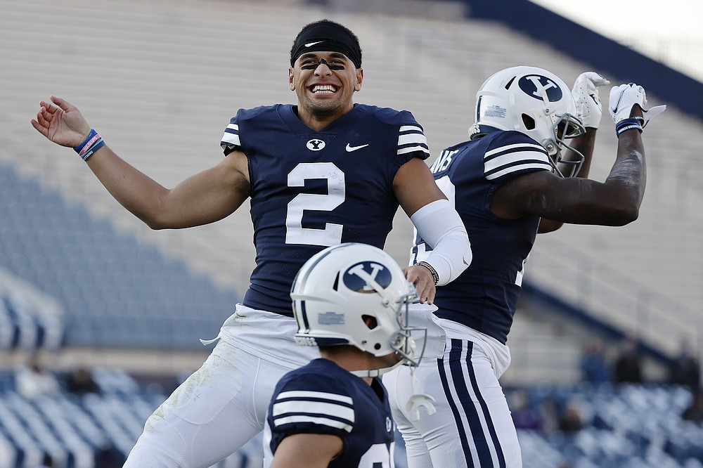 BYU wide receiver Neil Pau'u (2) congratulates running back Miles Davis, right, after his fourth quarter touchdown against North Alabama during an NCAA college football game Saturday, Nov. 21, 2020, in Provo, Utah. (AP Photo/Jeff Swinger, Pool)