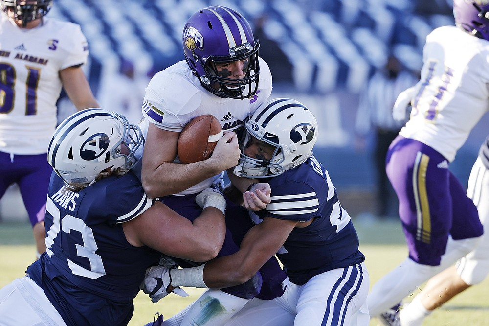 North Alabama quarterback Rett Files, center, is tackled by BYU defensive lineman Caden Haws, left and defensive back Tavita Gagnier (27) in the fourth quarter during an NCAA college football game Saturday, Nov. 21, 2020, in Provo, Utah. (AP Photo/Jeff Swinger, Pool)