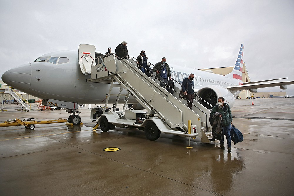 Journalists and American Airlines employees board a Boeing 737 Max at American Airlines Tulsa maintenance facility on Wednesday, December 2, 2020 in Tulsa, Okla.  Earlier, the plane had flown a group of journalists and American Airlines employees from Dallas to American Airlines Tulsa maintenance facility.  (Mike Simons / Tulsa World via AP)