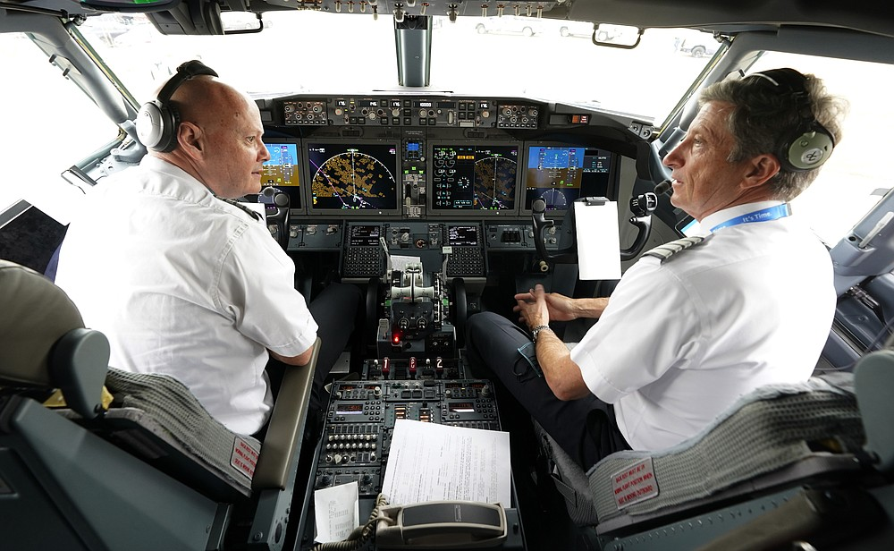 CORRECTING THE FIRST NAME OF PETE, NOT PET - American Airlines pilot Captain Pete Gamble, left and foreman John Konstanzer speaks in the cockpit of a Boeing 737 Max jet before taking off from Dallas Fort Worth Airport in Grapevine, Texas, Wednesday, December 2, 2020. American Airlines took its long-ground Boeing 737 Max jets out of storage, updated key flight control software and flew the aircraft in preparation for the first pay-per-flight flights later this month.  (AP Photo / LM Otero)
