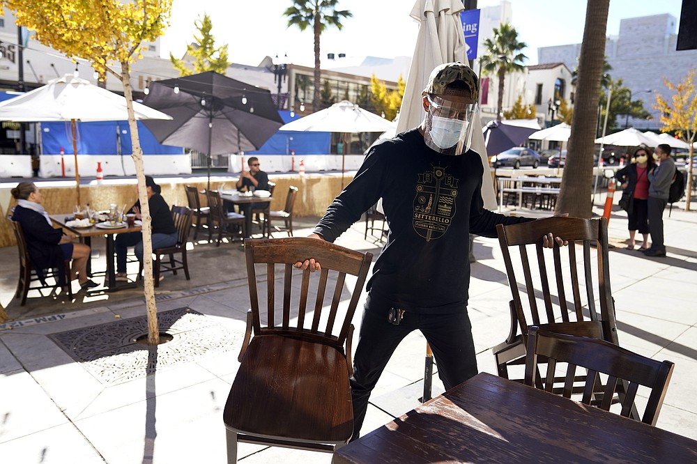 FILE - In this Dec. 1, 2020, file photo, General manager Damien Williams prepares outdoor seating at Settebello Pizzeria Napoletana in Pasadena, Calif. States faced a deadline on Friday, Dec. 4, 2020, to place orders for the coronavirus vaccine as many reported record infections, hospitalizations and deaths, while hospitals were pushed to the breaking point — with the worst feared yet to come. (AP Photo/Marcio Jose Sanchez, File)