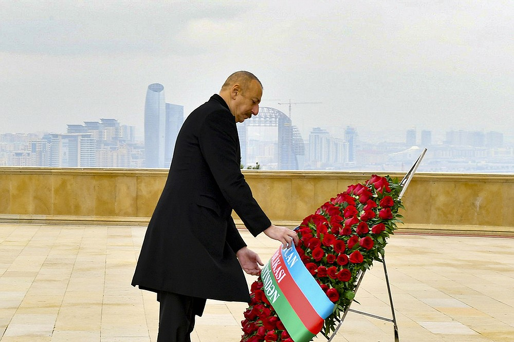 In this handout photo provided by the Azerbaijan's Presidential Press Office, Azerbaijani President Ilham Aliyev attends a laying ceremony at the Honorary Alley and the Alley of Martyrs in Baku, Azerbaijan, Friday, Dec, 4, 2020 Azerbaijan marked a day of remembrance for those who died in six weeks of fighting over Nagorno-Karabakh that ended with a Russia-brokered peace deal that saw Azerbaijan reclaim the territories that were held by Armenian forces for more than a quarter-century. (Azerbaijani Presidential Press Office via AP)