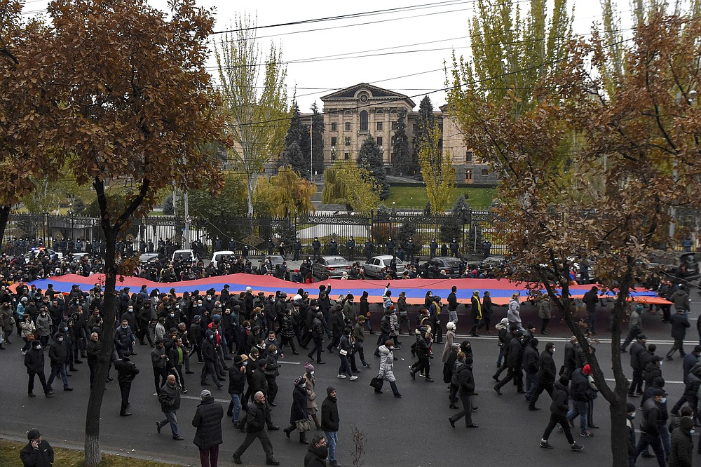 Opposition demonstrators carry a giant an Armenian national flag as they rally to pressure Armenian Prime Minister Nikol Pashinyan to resign over a peace deal with neighboring Azerbaijan in Republic Square in Yerevan, Armenia, Saturday, Dec. 5, 2020. Tens of thousands of opposition supporters marched across the Armenian capital Saturday to push for the resignation of the ex-Soviet nation's prime minister over his handling of the conflict with Azerbaijan over Nagorno-Karabakh. (Lusi Sargsyan/PHOTOLURE via AP)