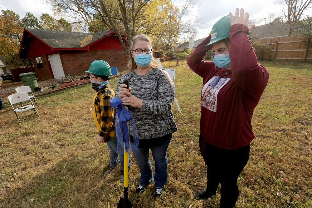 Zoe Griffis (from right), 17, stands with her mother Angela Sockrider and her brother Lyric Cote, 10, as they prepare to break ground Monday, November 9, 2020, during a Habitat for Humanity of Benton County ground breaking event for a new home for Sockrider at 808 N. 31st Street in Rogers. Check out nwaonline.com/201126Daily/ and nwadg.com/photos for a photo gallery.(NWA Democrat-Gazette/David Gottschalk)