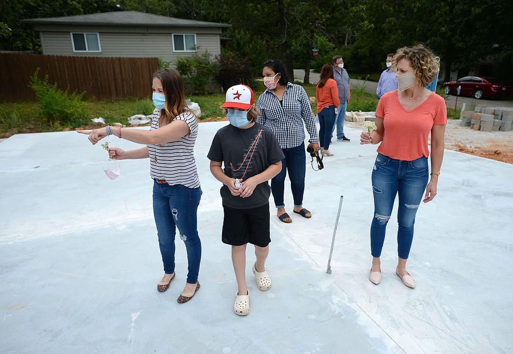 Homeowner Erica Kelso (from left) points out the planned layout of her master bedroom Friday, June 26, 2020, for her son, Louie, 10; daughter, Sophie, 7, (not pictured); and friends Carolina Vargas and Betina Henschell after a ceremony for the house's construction on Oak Road in Fayetteville. The house is being constructed by Habitat for Humanity of Washington County as the organization's 2020 Realtor Build house through a partnership with local real estate and industry partners and volunteers. Visit nwaonline.com/200627Daily/ for today's photo gallery. (NWA Democrat-Gazette/Andy Shupe)