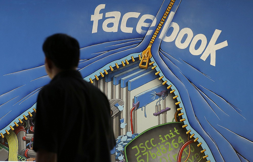FILE - In this June 11, 2014, file photo, a man walks past a mural in an office on the Facebook campus in Menlo Park, Calif. Federal regulators asked Wednesday, Dec. 9, 2020, for Facebook to be ordered to divest its Instagram and WhatsApp messaging services as the U.S. government and 48 states and districts accused the company of abusing its market power in social networking to crush smaller competitors. The antitrust lawsuits were announced by the Federal Trade Commission and New York Attorney General Letitia James. (AP Photo/Jeff Chiu, File)