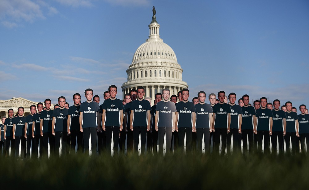 """FILE - In this April 10, 2018, file photo, life-sized cutouts depicting Facebook CEO Mark Zuckerberg wearing """"Fix Fakebook"""" T-shirts are displayed by advocacy group, Avaaz, on the South East Lawn of the Capitol on Capitol Hill in Washington, ahead of Zuckerberg's appearance before a Senate Judiciary and Commerce Committees joint hearing. Federal regulators asked Wednesday, Dec. 9, 2020, for Facebook to be ordered to divest its Instagram and WhatsApp messaging services as the U.S. government and 48 states and districts accused the company of abusing its market power in social networking to crush smaller competitors. The antitrust lawsuits were announced by the Federal Trade Commission and New York Attorney General Letitia James. (AP Photo/Carolyn Kaster, File)"""