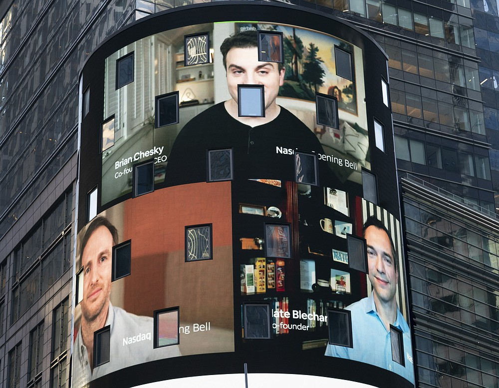 The electronic screen at the Nasdaq MarketPlace displays the Airbnb co-founders Brian Chesky, top, Joe Gebbia, left, and Nathan Blecharczyk, right, Thursday, Dec. 10, 2020, in New York. The San Francisco-based online vacation rental company holds its IPO Thursday. (AP Photo/Mark Lennihan)