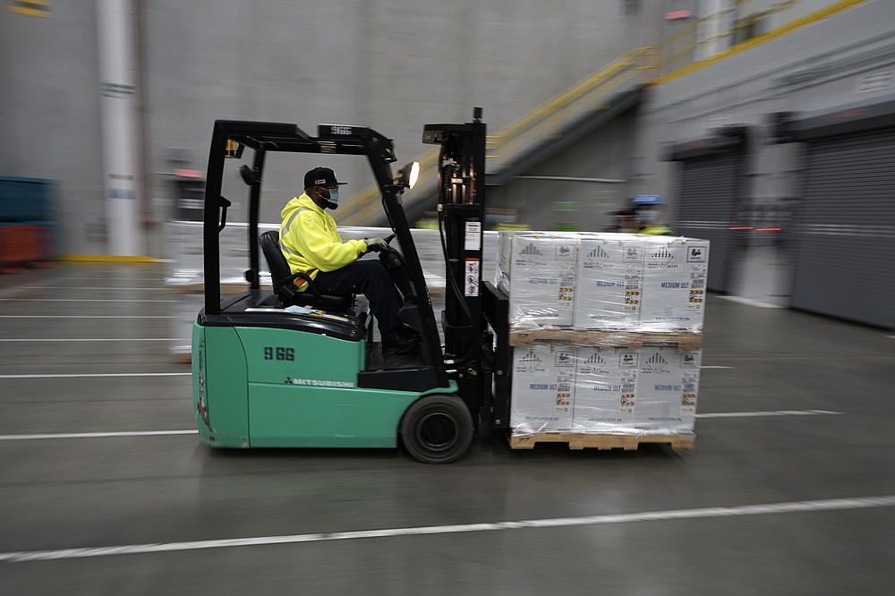 Boxes containing the Pfizer-BioNTech COVID-19 vaccine are brought to to the loading dock for shipping at the Pfizer Global Supply Kalamazoo manufacturing plant in Portage, Mich., Sunday, Dec. 13, 2020. (AP Photo/Morry Gash, Pool)