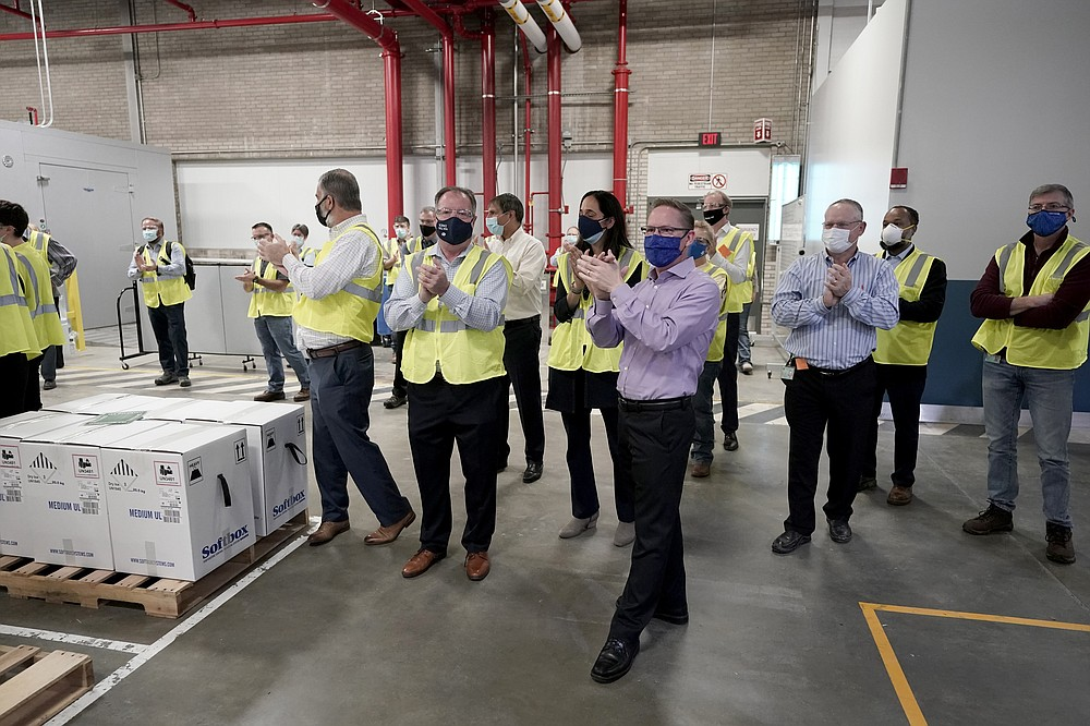Pfizer employees clap after line workers finished packing boxes containing the Pfizer-BioNTech COVID-19 vaccine to be shipped at the Pfizer Global Supply Kalamazoo manufacturing plant in Portage, Mich., Sunday, Dec. 13, 2020. (AP Photo/Morry Gash, Pool)