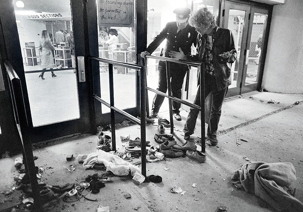 FILE - In this Dec. 3, 1979, file photo, a security guard and an unidentified man look at an area where several people were killed as they were caught in a surging crowd entering Cincinnati's Riverfront Coliseum for a concert by the British rock band The Who. Alumni of nearby Finneytown High School, who lost three classmates in the tragedy, faced obstacles in 2020 to their annual memorial scholarship fund-raising event. In the end, they created a show of prerecorded video interviews with The Who's frontman, Roger Daltrey, guitarist-songwriter Pete Townshend and a mix of recorded and live discussions with relatives of the 11 people killed in the tragedy. (AP Photo/Brian Horton, File)